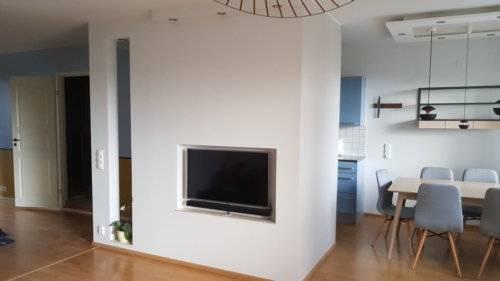 Väliseinän design: tv- aukko, valokotelot ja hyllypaikka josta näkee toiseen huoneeseen